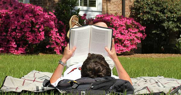 Student with book on lawn